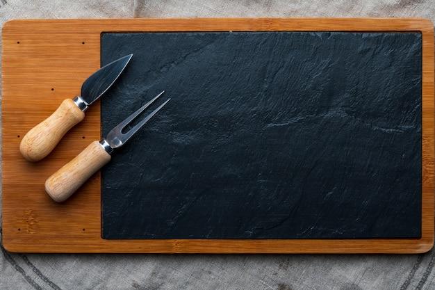 치즈 및 기타 개구부를위한 빈 테이블. copyspace. 치즈에 대 한 칠판 포크와 나이프 상위 뷰입니다.
