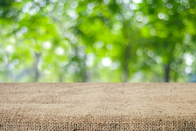 Empty table and sack tablecloth over blur tree with bokeh background