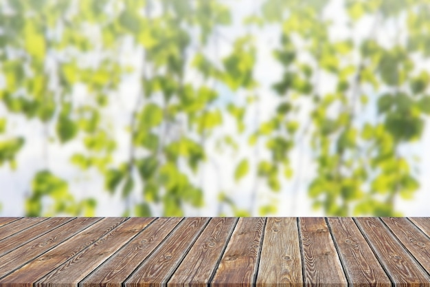 Empty table top on blurred background of green branches.