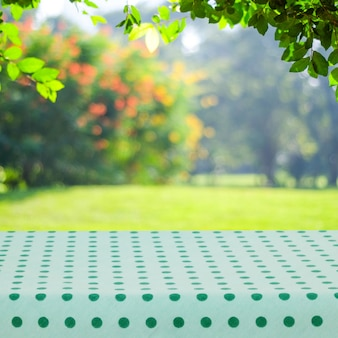 Empty table with green polka dot tablecloth over blur park with bokeh