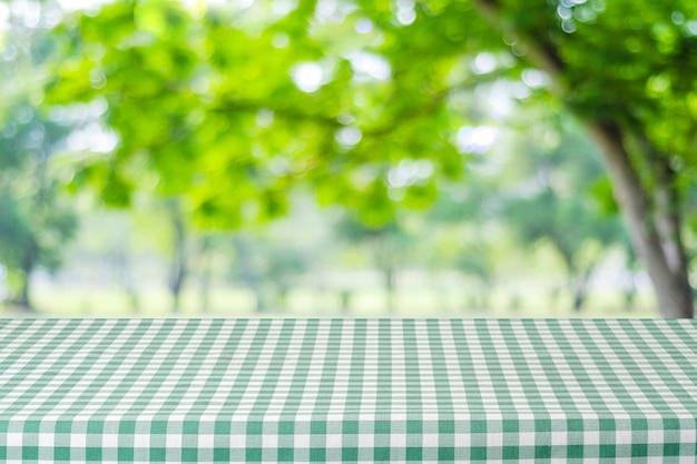 음식과 제품 디스플레이 몽타주, 봄, 여름 시즌 흐림 정원과 나뭇잎 배경 위에 녹색 식탁보와 빈 테이블