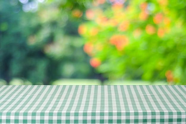 흐림 정원 및 bokeh 배경 위에 녹색 식탁보와 빈 테이블