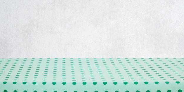 녹색 흰색 벽 배경 위에 녹색 식탁보와 빈 테이블