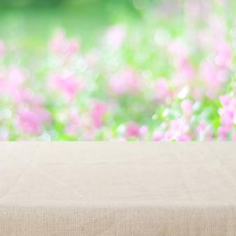 흐림 정원과 꽃 배경 위에 린넨 식탁보와 빈 테이블