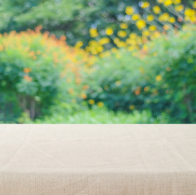 Empty table with linen tablecloth over vintage cement wall background