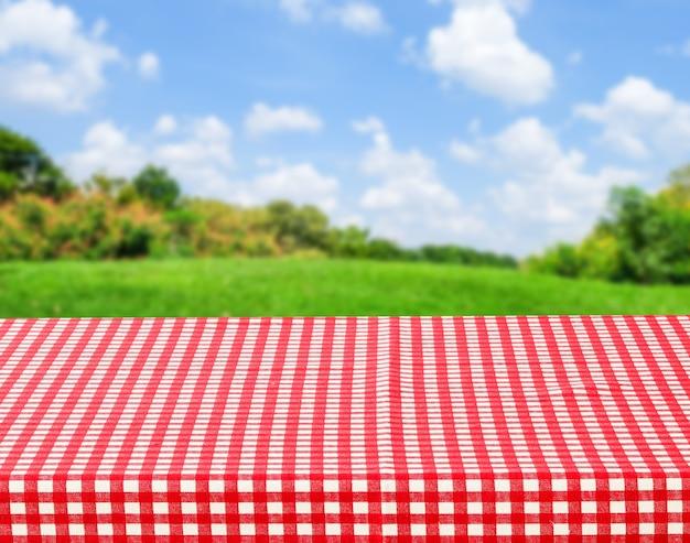 흐릿한 공원 자연 배경 위에 빨간색과 흰색 식탁보가 있는 빈 테이블