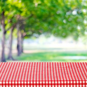 흐리게 공원에 빨간색과 흰색 식탁보와 빈 테이블