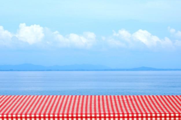 흐린 바다 야외에 빨간색과 흰색 식탁보와 빈 테이블