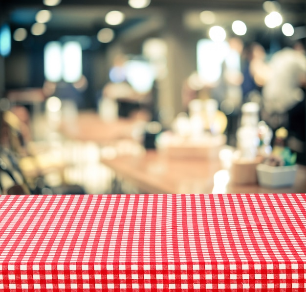 Empty table with red check table cloth over blurred cafe background