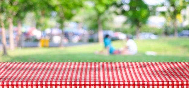 사람과 bokeh 배경 흐림 공원을 통해 빨간색 체크 식탁보와 빈 테이블