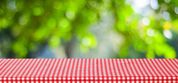 음식과 제품 디스플레이 몽타주 배경, 배너 흐림 녹색 나무와 나뭇잎 배경 위에 빨간색 식탁보와 빈 테이블