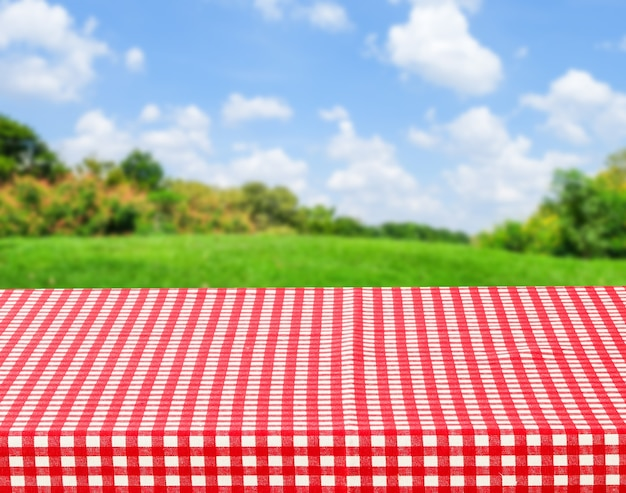 Empty table with red and white tablecloth over blurred park nature background