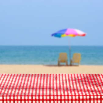 Empty table with red and white tablecloth over blurred sea outdoor nature background, for product display montage, summer