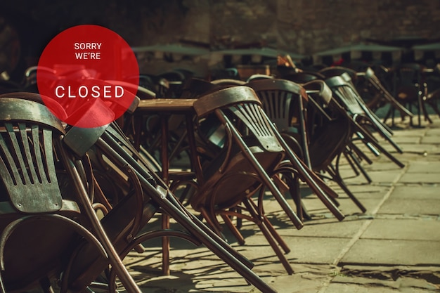 코로나바이러스로 인해 폐쇄된 거리 레스토랑의 빈 테이블과 의자. 빨간 둥근 기호