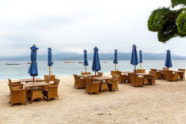 Empty tables of the beach cafe. folded umbrellas, lack of tourists.