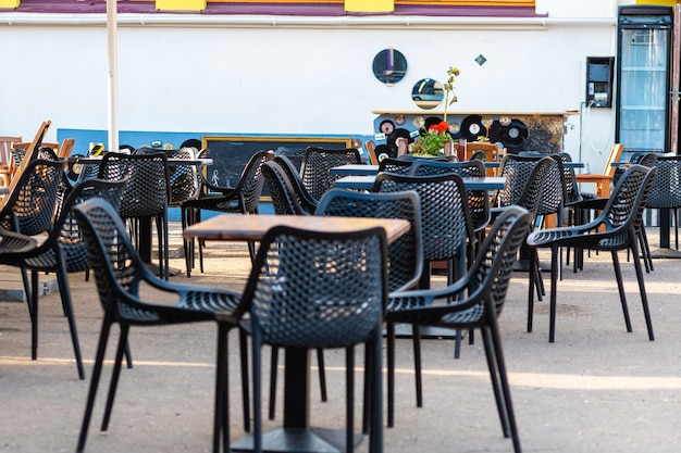 Empty tables and chairs at a outdoor restaurant in sunny day