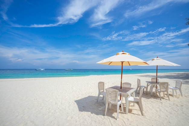 Empty tables and chairs with umbrella on the beach, near the sea.
