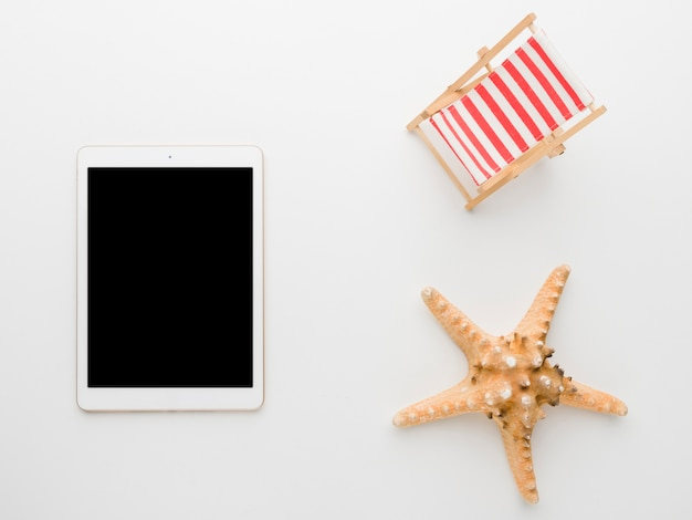 Empty tablet and marine starfish on white background