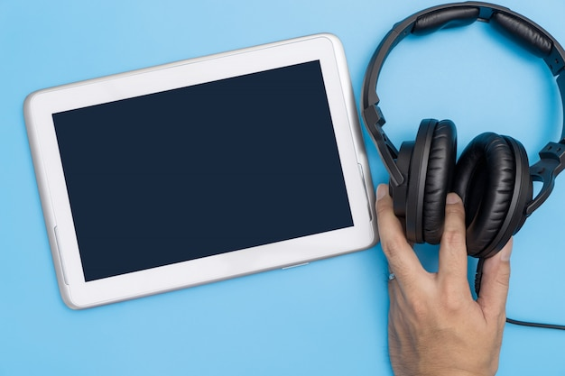 Empty tablet with hand holding headphone for music and video streaming concept