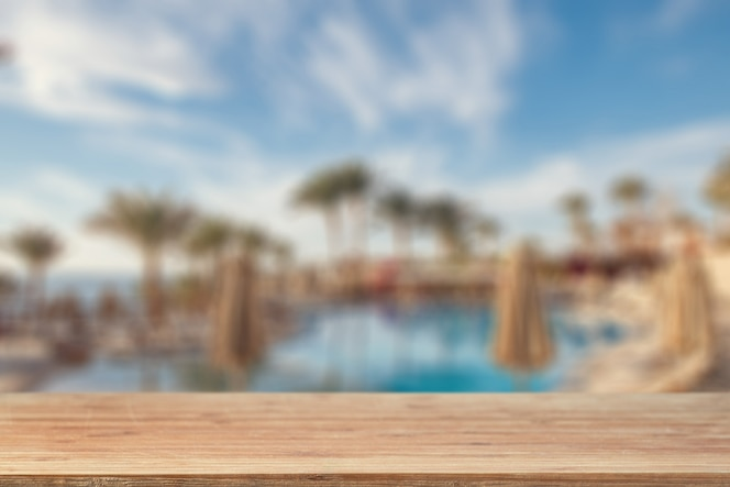 Empty tabletop against the background of a swimming pool, palm trees and sea beach