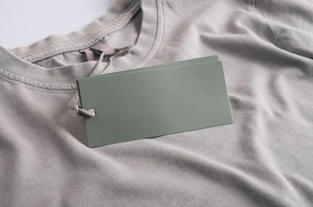 Empty tag card or label mockup on gray clothes