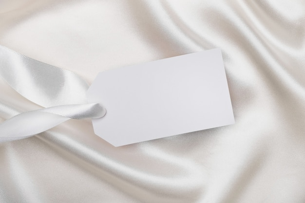 Empty tag card for text on white silk fabric. mockup for design