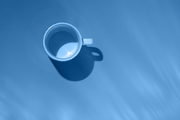 Empty tea cup on blue paper. trendy color of the year.