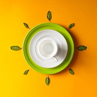 オレンジ色の壁に緑の葉と空のティーカップ。時間の概念。