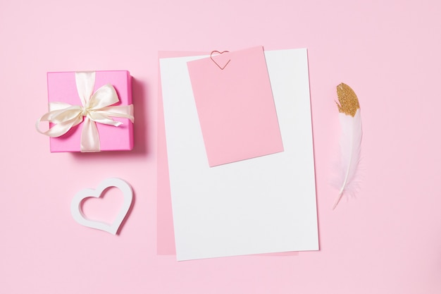 Empty template for romantic letters on a pink space. white feather with gold plating