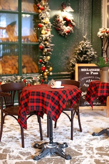 Empty terrace of cafe with wooden table and chair decorated for christmas.