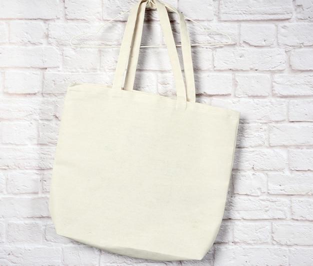 Пустой текстильный эко-мешок, висящий у белой кирпичной стены, без пластика, без отходов