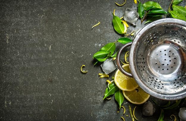 Опустошите кастрюлю листьями, нарезанным лимоном, цедрой и льдом. на каменном столе. свободное место для текста. вид сверху