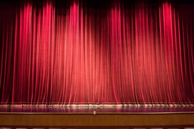 Empty theater stage and red curtain or drapes background