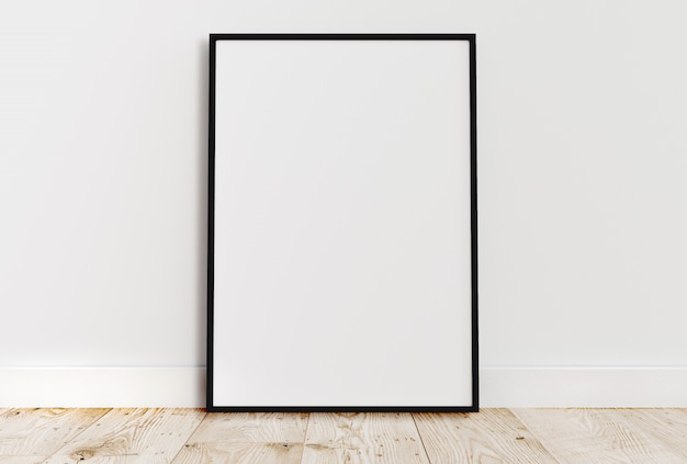 Empty thin black frame on light wooden floor with white wall behind it.