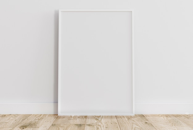 Empty thin white frame on light wooden floor with white wall behind it.