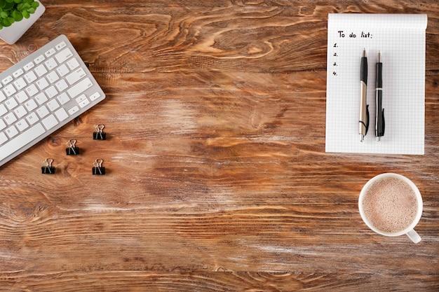 Пустой список дел с чашкой кофе и компьютерной клавиатурой на деревянном