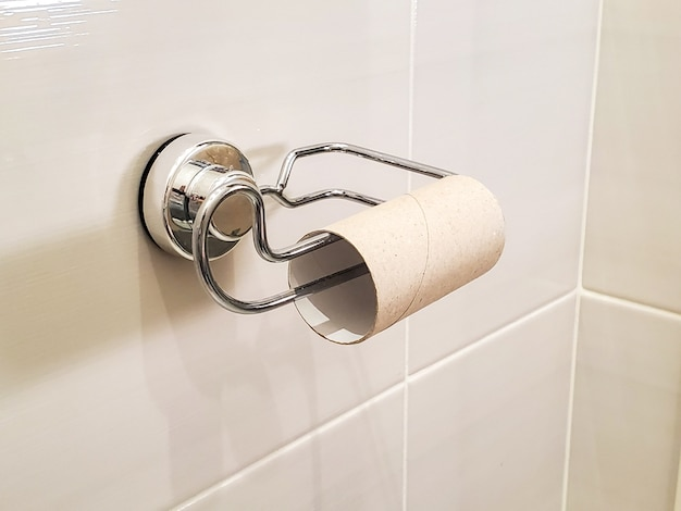 An empty toilet paper tube hangs on a chrome holder in the toilet