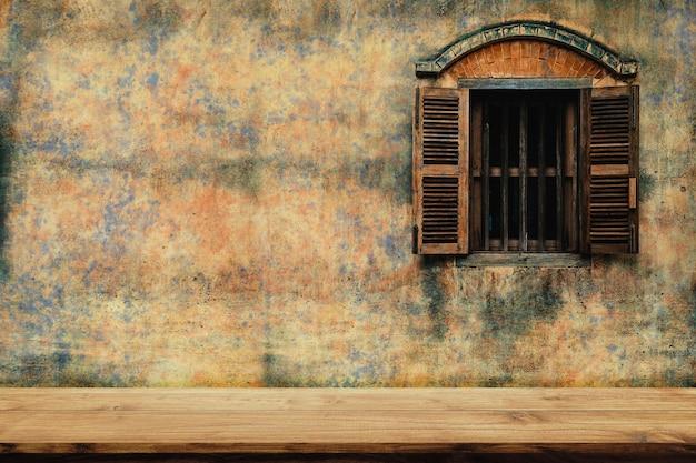 오래 된 시멘트 벽과 나무 창 배경으로 나무 의자의 빈 상단.