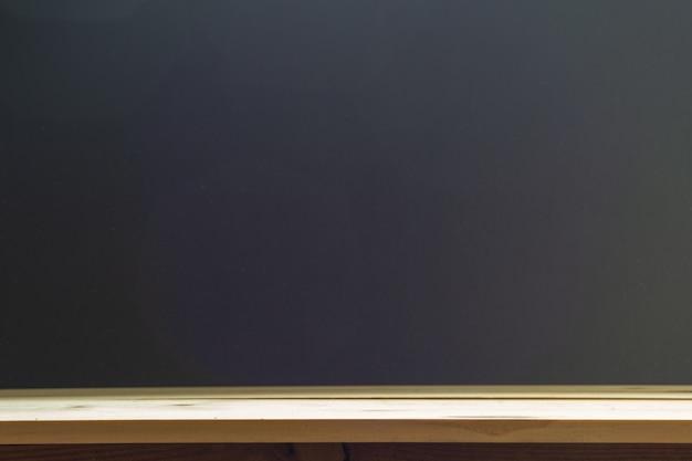 Empty top shelves or table wood on blackboard background.