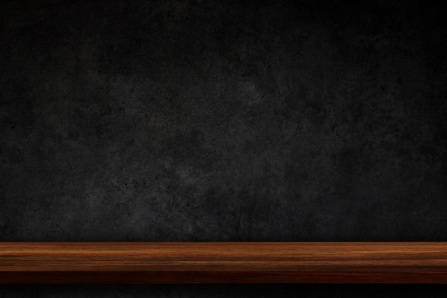 Empty top of wooden shelves on dark concrete wall background