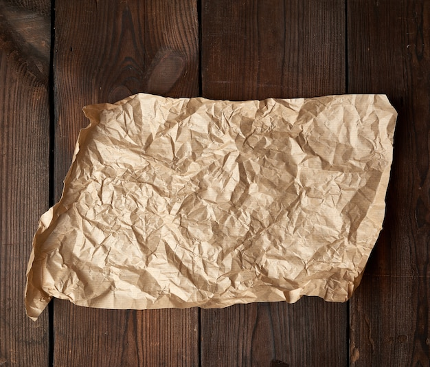 Empty torn piece of brown crumpled baking paper on a table of boards