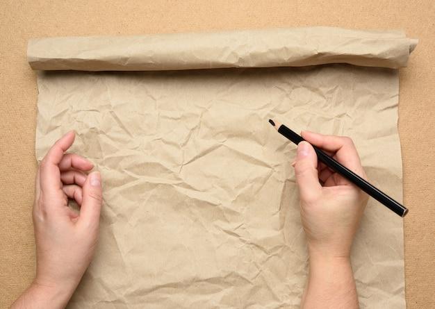 Пустой порванный лист коричневой крафт-бумаги и две руки с черным деревянным карандашом, деревянный стол, вид сверху, место для надписи