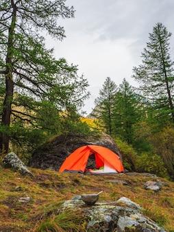 숟가락이 든 빈 관광 그릇은 오렌지색 텐트와 높은 산이 있는 숲을 배경으로 돌 위에 놓여 있습니다. 점심 시간, 고지대 트레킹.