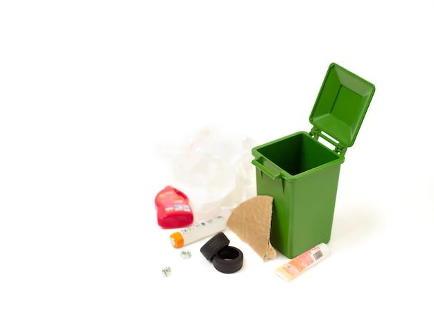 Пустой мусорный бак и разбросанный мусор на белом фоне