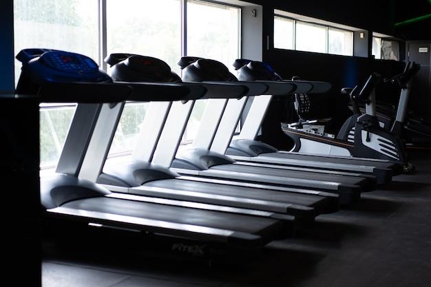 大きな窓の近くの空のトレッドミルスタンディングジム誰もフィットネススポーツ健康的なライフスタイルの概念