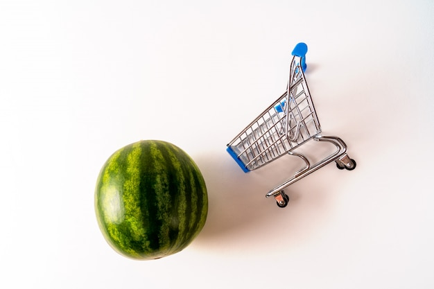 Empty trolley shopping cart and small seedless watermelon isolated on white background.