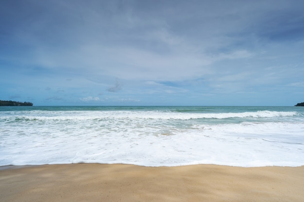 Empty tropical summer beach background horizon with sky and white sand beach wave crashing on sandy shore.