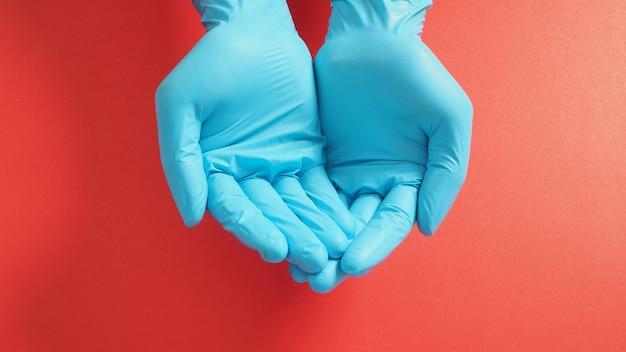 赤い背景で助けを求めるサインをしている手袋で両手を空にします。