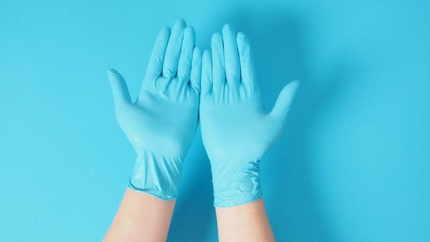 青い背景に手袋をはめて両手を空にします。