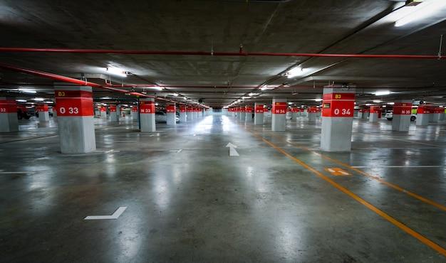 Пустая подземная автостоянка. подземный гараж в торговом центре или в международном аэропорту. крытая парковка. бетонный цокольный этаж, гараж.